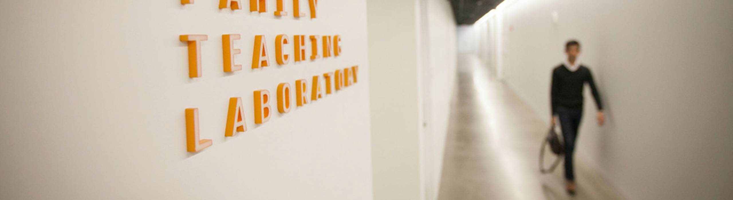 A student walks a long corridor within Gates Hall.
