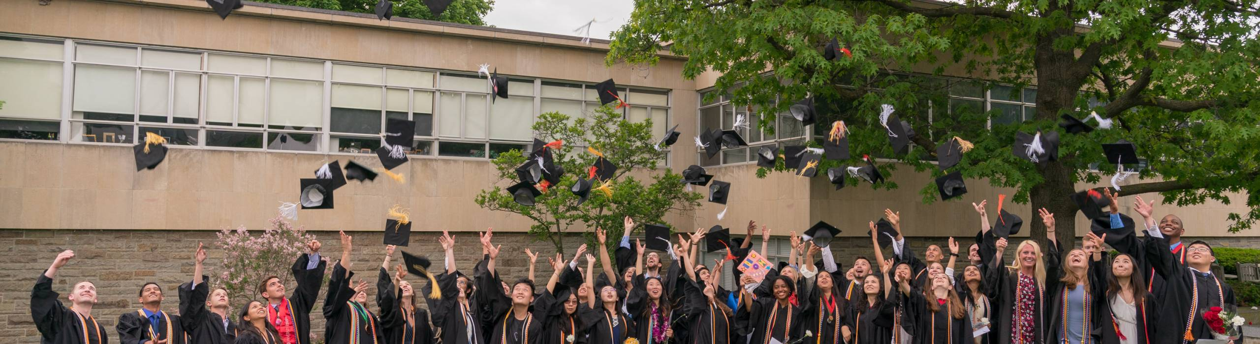 Info Sci's Class of 2018 graduates toss their caps during Commencement ceremonies on Saturday, May 26, 2018, on the Cornell campus in Ithaca.