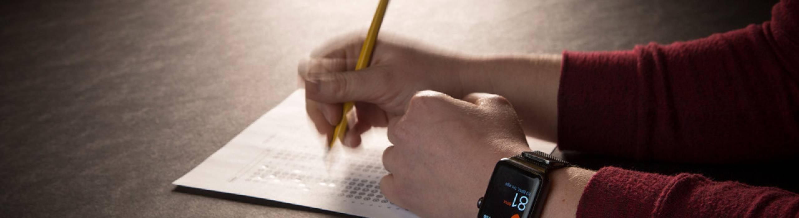 A student wears an Apple watch while taking an exam.
