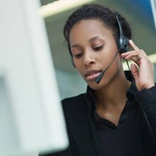 A woman with a hands-free headset answers a phone call.
