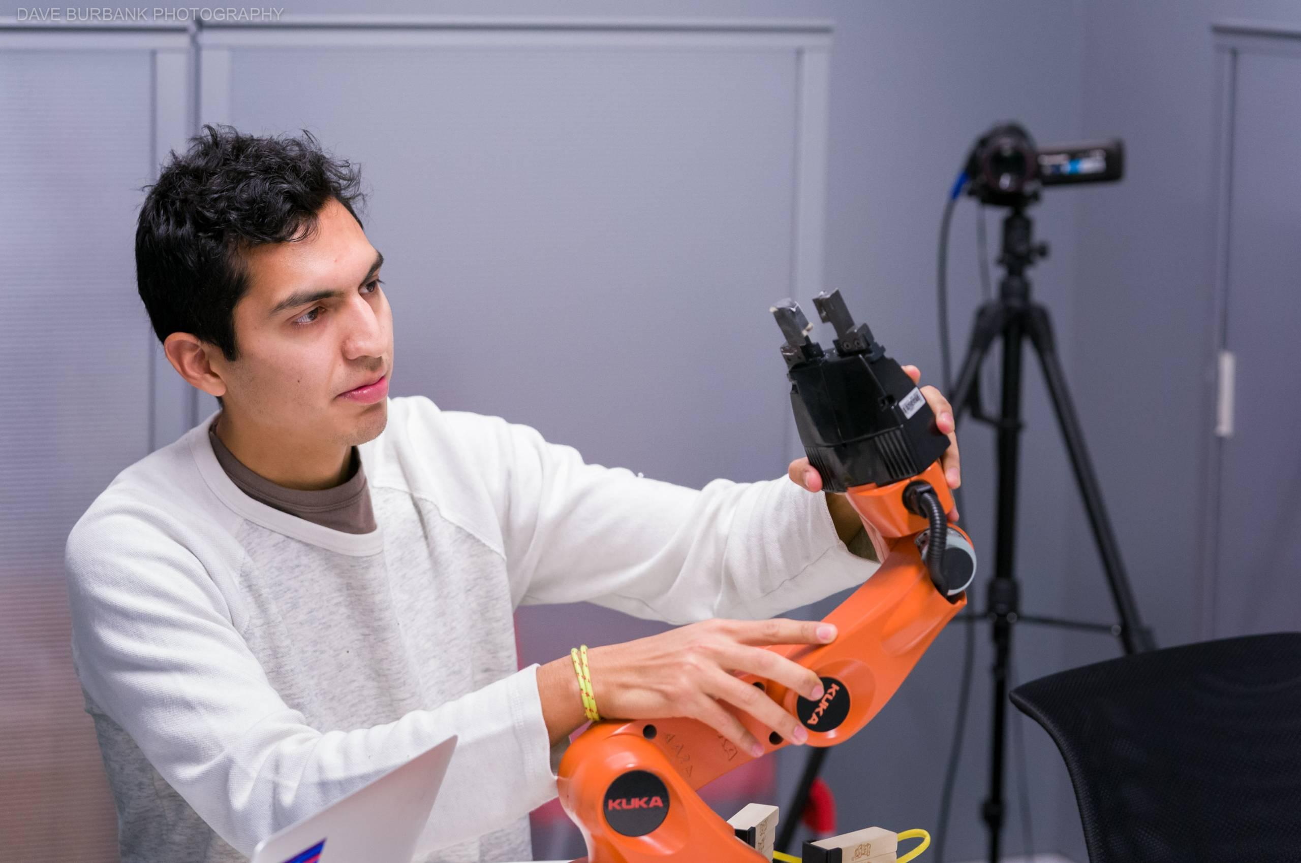 Cornell PhD candidate Houston Claure makes adjustments to a robot used in the Information Science's Robot in Groups Lab in Gates Hall.